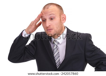 Depressed, unshaved businessman raising his hand at his head in disbelief at his bad fortune, isolated on white - stock photo
