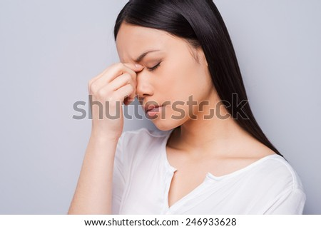 Depressed woman. Depressed young Asian woman touching her head with hands and keeping eyes closed while standing against grey background - stock photo