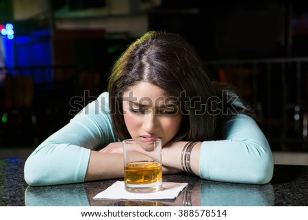 Depressed woman having whiskey at bar counter in bar