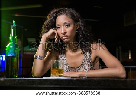 Depressed woman having whiskey drink at bar counter in bar