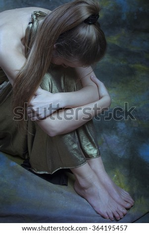 depressed woman in long elegant golden dress  sit on  floor,  full body shot, above
