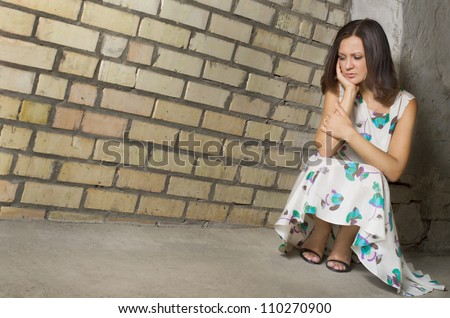 Depressed woman seeking solitude crouched low against a brick wall with her chin on her hand and downcast eyes - stock photo