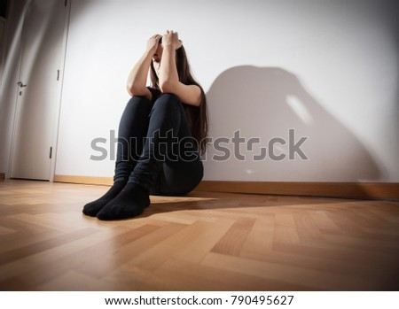 Depressed woman sitting on floor in empty room, female suffering from depression