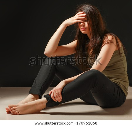 Depressed woman sitting on floor isolated on black background - stock photo