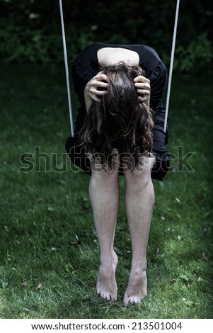 Depressed woman sitting on the swing, holding her head - stock photo