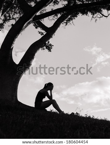 Depressed woman sitting under the tree outdoors. - stock photo