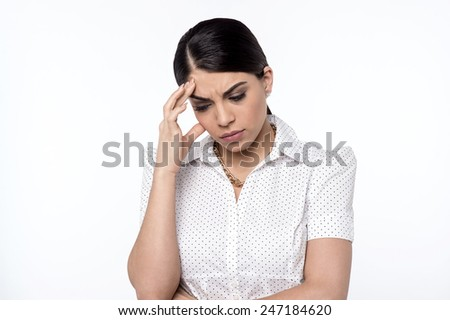 Depressed woman touching her forehead - stock photo