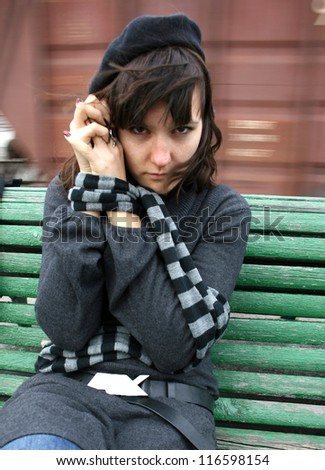 Depressed woman with captive hands. She is on railway station.