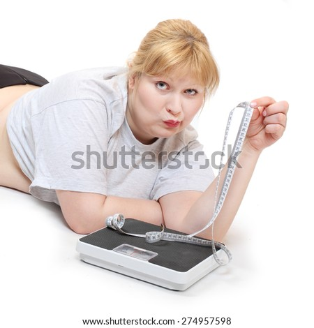 Depressed woman with measure tape and weight scale. - stock photo