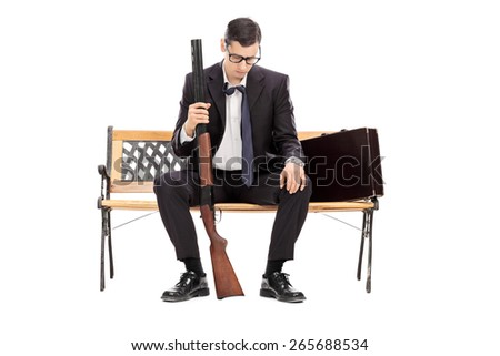 Depressed young businessman holding a shotgun rifle and looking down seated on a wooden bench isolated on white background - stock photo