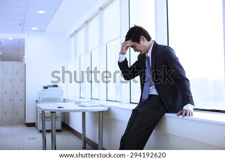 Depressed young businessman in office - stock photo