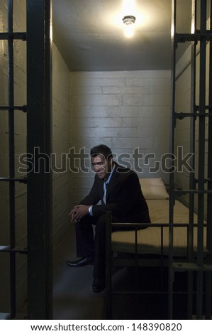 Depressed young businessman sitting on bed in prison - stock photo