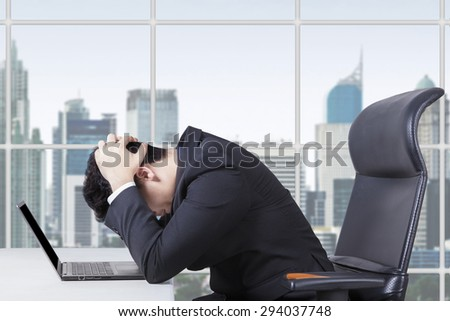 Depressed young businessman wearing formal suit, sitting in the office with a laptop on desk