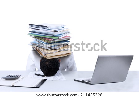 Depressed young businessman with a pile of documents on his head at office - stock photo