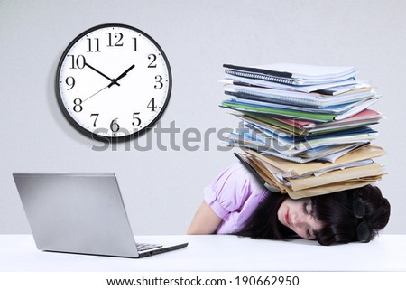 Depressed young businesswoman with a pile of documents on her head at office - stock photo