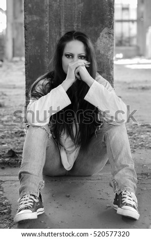 Depressed young girl sitting on the concrete floor of the abandoned building in black and white.