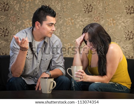 Depressed young Hispanic woman in conversation with man - stock photo