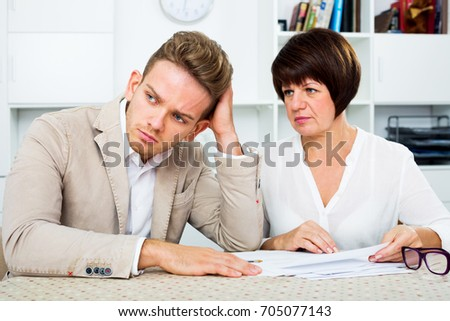 Depressed young man and mature woman sit at table and discuss legal aspects of paperwork. Focus on the man