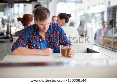 Depressed young man drinking beer in a bar - stock photo