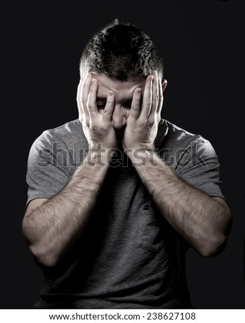 depressed young man in stress suffering migraine and headache in intense pain feeling desperate and sick with hands covering face on black studio background - stock photo