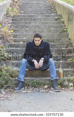 Depressed young man sitting on concrete stairways with bottle of alcohol drink beside him - stock photo