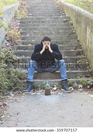 Depressed young man sitting on outdoor stairway with bottle of alcohol drink in front of him