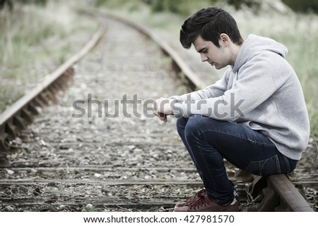 Depressed Young Man Sitting On Railway Track - stock photo