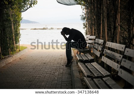 depressed young man sitting on the bench - stock photo