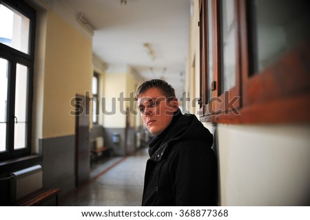 Depressed young man standing in hall.   Waiting room - stock photo