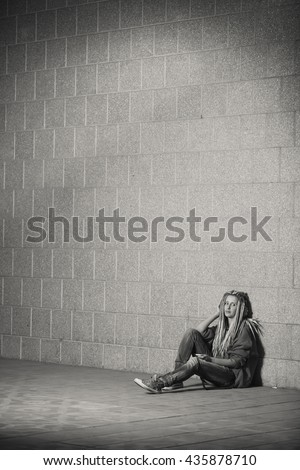 Depressed young teenage girl in hood sitting down on road in th city. Alone in the big city. - stock photo