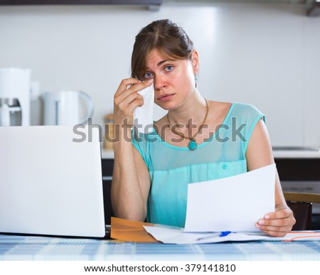 Depressed young woman at kitchen receiving bank refuse about delay of payment