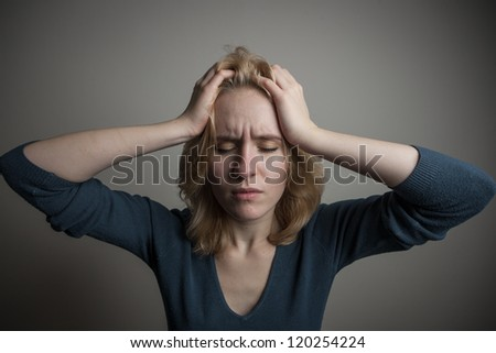 Depressed young woman desperately holding her head, suffering from headache - stock photo