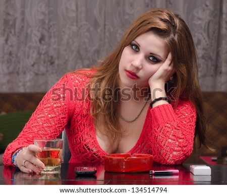 Depressed young woman drinking and smoking. - stock photo
