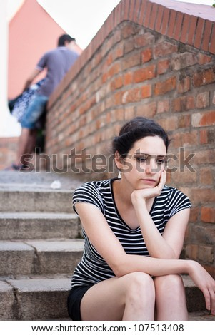 Depressed young woman sitting in an urban area