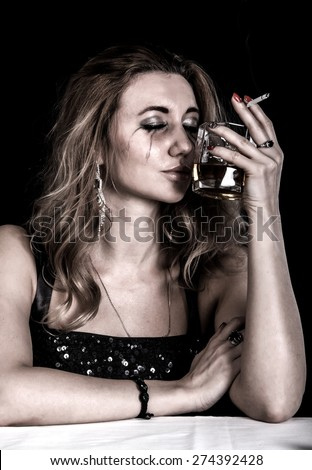 Depressed young woman with a glass of whiskey and a cigarette over black background