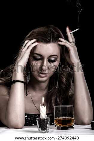 Depressed young woman with a glass of whiskey and a cigarette over black background - stock photo