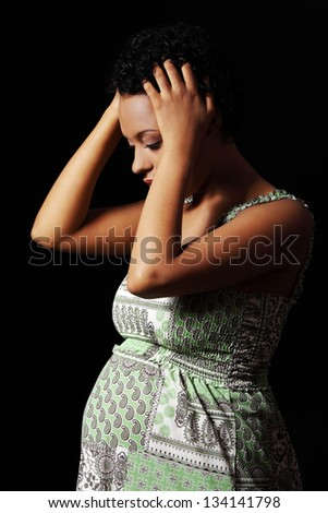 Depression and stress of young pregnant woman against black background - stock photo