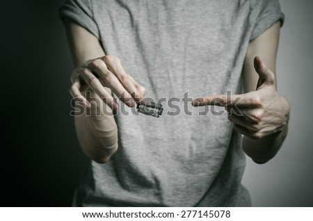 Depression and suicide theme: man holding a razor to suicide on a gray background in the studio