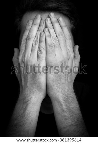 Depression concept â?? man covering face with hands - stock photo