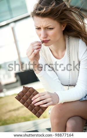 Depression - outdoor portrait of young worried woman eating chocolate - stock photo