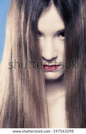 Depression. Portrait of sad emotional girl. Young woman covering her face with long hair on blue. Studio shot.