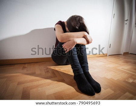 Depression teenager sitting on floor in empty room