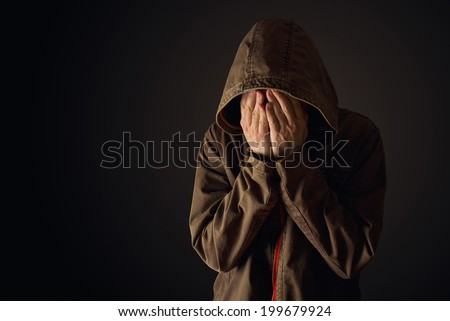Depressive man in hooded jacket crying with hands covering his face, looking upset and showing remorse - stock photo