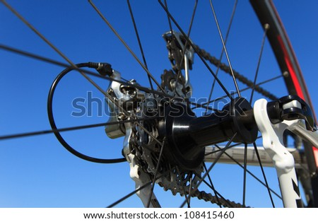 Derailleur and rear wheel of a modern racing bike, with a clear blue sky.