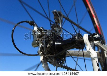 Derailleur and rear wheel (spinning) of a modern racing bike, with a clear blue sky. Shallow D.O.F.