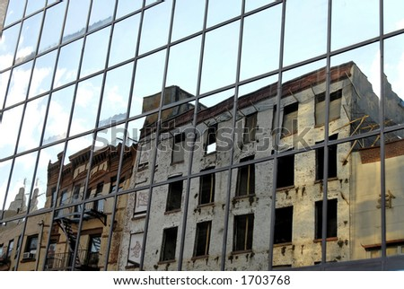 Derelict buildings reflected in modern office tower in New York's Chinatown - stock photo