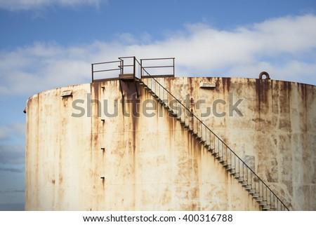 Derelict oil storage tank. - stock photo