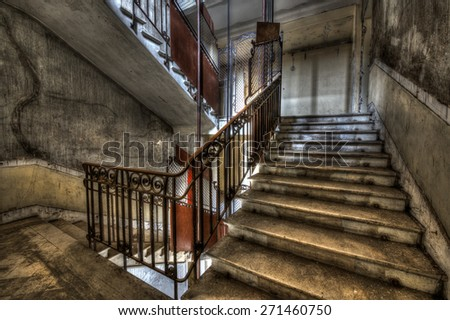 Derelict stairwell in an abandoned building, HDR processing - stock photo