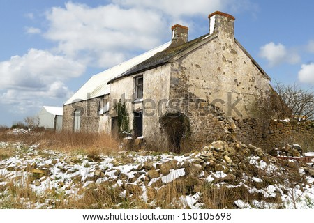 Derict farm building in South Wales, UK. Snow on ground. - stock photo