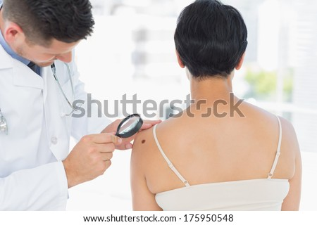 Dermatologist examining melanoma on woman with magnifying glass in clinic - stock photo